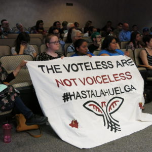 Supporters of immigrants' rights held a banner on Tuesday as Kalamazoo County commissioners discussed a resolution on family separations. CREDIT SEHVILLA MAN / WMUK